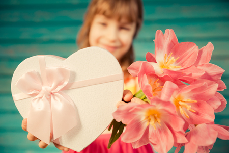 box: Beautiful child with bouquet of flowers against wooden background. Spring family holiday concept. Mothers day