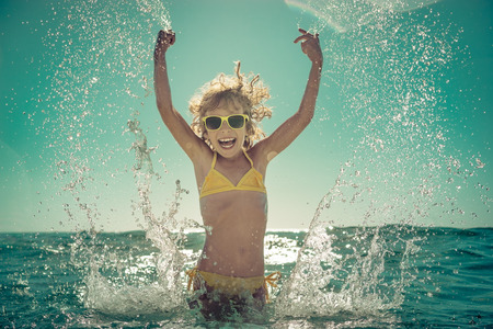 1: Happy child playing in the sea. Kid having fun at the beach. Summer vacation and active lifestyle concept