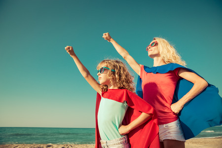 super woman: Family of superheroes on the beach. Mother and daughter having fun outdoor. Summer vacation concept Stock Photo