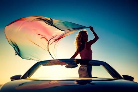 aspirational: Silhouette of young woman at the beach. Girl with flying fabric against sunset sky and sea background. Female traveling by car. Summer vacation and travel concept