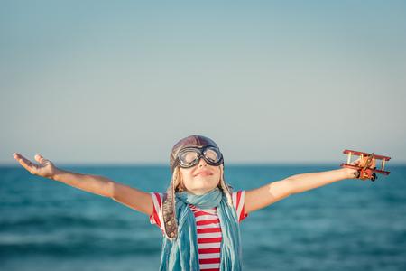Gelukkig kind spelen met speelgoed vliegtuig tegen de zee en hemel achtergrond. Kid piloot plezier outdoor. Zomer vakantie en reizen concept. Vrijheid en verbeelding