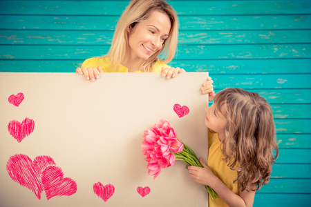 greeting season: Woman and child with bouquet of flowers against green background. Spring family holiday concept. Mothers day