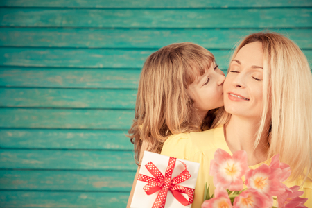 mama e hija: Mujer y niño con el ramo de flores contra el fondo verde. Familia del resorte concepto de vacaciones. Día de la Madre