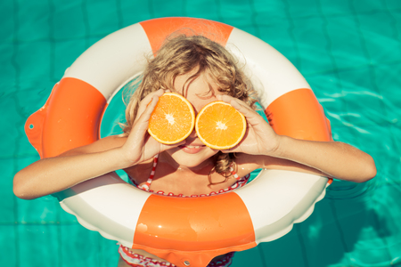 fruit: Child with orange outdoor. Kid having fun in swimming pool. Summer vacation and healthy eating concept