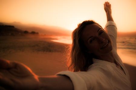 ビーチで若い女性のシルエット。夕焼け空と海の背景の女の子。夏休み、旅行のコンセプト 写真素材