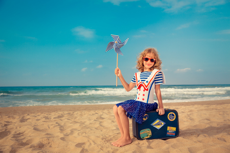 freedom: Child pretend to be sailor. Happy kid playing outdoor on the beach. Girl against sea and sky background. Summer vacation and travel concept