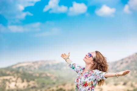 Gelukkige vrouw met open handen tegen blauwe zee en hemelachtergrond. Persoon met plezier op zomervakantie. Vrijheid en verbeeldingskoncept