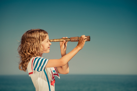 Happy child with vintage spyglass. Kid having fun on summer vacation. Travel and adventure concept