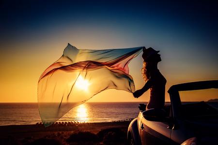 Silhouet van een jonge vrouw op het strand. Meisje met vliegende stof tegen zonsondergang hemel en zee achtergrond. Vrouw met de auto reist. Zomer vakantie en reizen concept