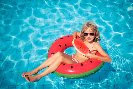 Child with watermelon outdoor. Kid having fun in swimming pool. Summer vacation and healthy eating concept Banco de Imagens