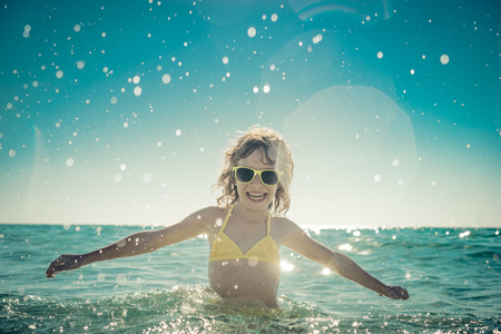 children party: Happy child playing in the sea. Kid having fun at the beach. Summer vacation and active lifestyle concept