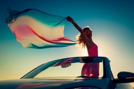 Silhouet van een jonge vrouw op het strand. Meisje met vliegende stof tegen zonsondergang hemel en zee achtergrond. Vrouw met de auto reist. Zomer vakantie en reizen concept Stockfoto - 77689903
