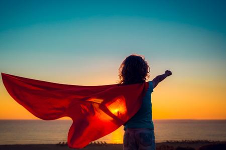 Niño de superhéroes en la playa. chico súper héroe que se divierten al aire libre. concepto de vacaciones de verano Foto de archivo - 77689707