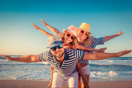 voyage: Bonne famille sur la plage. Les gens s'amusent pour les vacances d'été. Père, mère et enfant contre la mer bleue et le fond du ciel. Concept de voyage de vacances