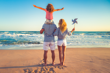 ビーチで幸せな家族。夏休みに楽しいを持っている人々。父、母と青い海と空の背景の子。休暇旅行の概念 写真素材 - 78281259