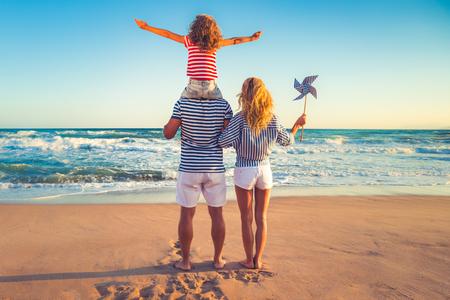 Glückliche Familie am Strand. Die Leute haben Spaß auf Sommerferien. Vater, Mutter und Kind gegen blauen Meer und Himmel Hintergrund. Urlaubsreisekonzept