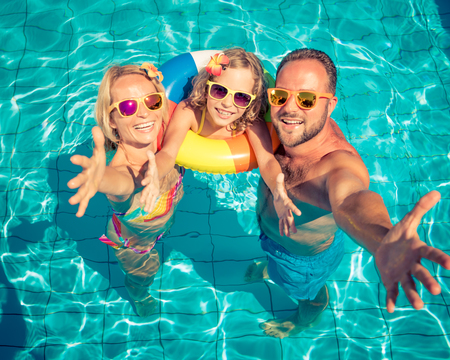 Happy family having fun on summer vacation. Father, mother and child playing in swimming pool. Active healthy lifestyle concept