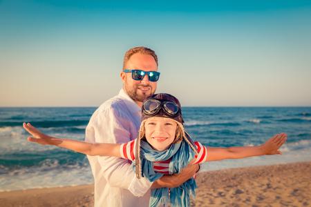 voyage: Bonne famille sur la plage. Les gens s'amusent pour les vacances d'été. Père et enfant contre la mer bleue et le fond du ciel. Concept de voyage de vacances
