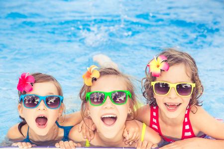 Glückliche Kinder im Swimmingpool. Lustige Kinder spielen im Freien. Sommerferien Konzept Standard-Bild - 78281283