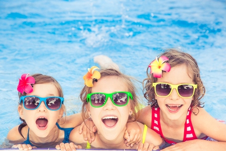 Happy children in the swimming pool. Funny kids playing outdoors. Summer vacation concept Banco de Imagens - 78281283