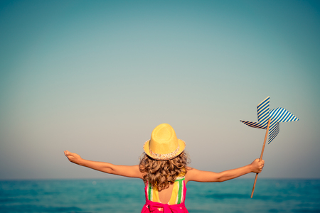 1 person: Happy child with open hands against blue sea and sky background. Kid having fun on summer vacation. Freedom and imagination concept Stock Photo