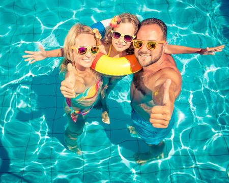 Gelukkige familie met plezier op zomervakantie. Vader, moeder en kind spelen in het zwembad. Actief gezond levensstijl concept
