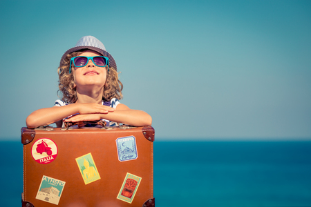 Happy child with vintage suitcase. Kid having fun on summer vacation. Travel and adventure concept