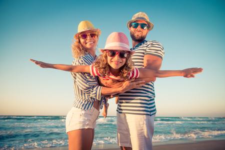 ビーチで幸せな家族。夏休みに楽しいを持っている人々。父、母と青い海と空の背景の子。休暇旅行の概念