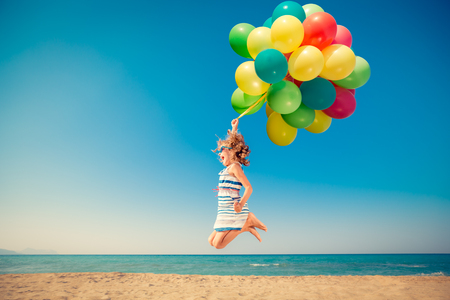 Happy child jumping with colorful balloons on sandy beach. Portrait of funny girl against blue sea and sky background. Active kid having fun on summer vacation. Freedom and imagination concept