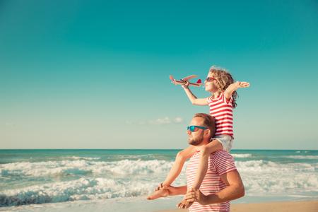 ビーチで幸せな家族。夏休みに楽しいを持っている人々。父と青い海と空の背景の子。休暇旅行の概念
