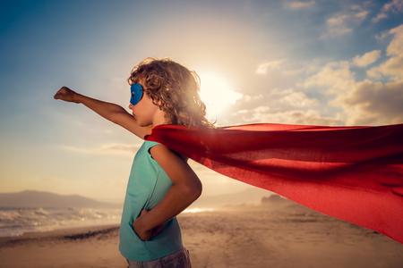 Superhero child on the beach. Super hero kid having fun outdoor. Summer vacation concept