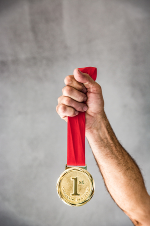 Senior man holding medal in hand. Win and success concept photo