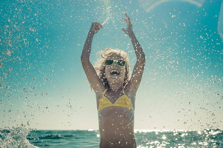 freedom: Happy child playing in the sea. Kid having fun at the beach. Summer vacation and active lifestyle concept