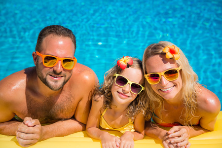 Happy family having fun on summer vacation. Father, mother and child playing in swimming pool. Active healthy lifestyle concept Stok Fotoğraf - 78453787