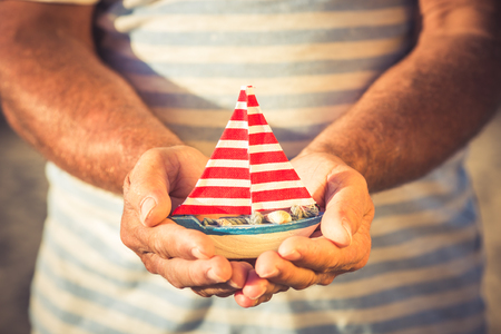 Senior sailor holding handmade sailing boat in hands against sea background. Summer vacation and travel concept photo