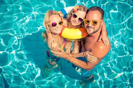 Famiglia felice divertirsi durante le vacanze estive. Padre, madre e bambino che giocano in piscina. Concetto di stile di vita sano attivo Archivio Fotografico - 78453790