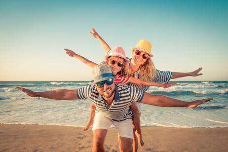 Bonne famille sur la plage. Les gens s'amusent pour les vacances d'été. Père, mère et enfant contre la mer bleue et le fond du ciel. Concept de voyage de vacances Banque d'images - 78590202