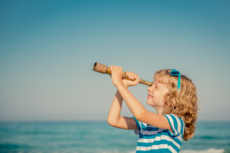 1 person: Child pretend to be sailor. Happy kid playing outdoor against sea and sky background. Summer vacation and travel concept