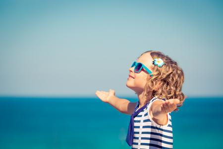 voyage: Enfant heureux avec les mains ouvertes contre la mer bleue et le fond du ciel. Enfant s'amuser sur les vacances d'été. Concept de liberté et d'imagination