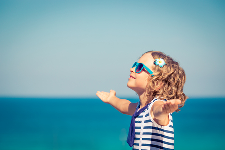 freedom: Happy child with open hands against blue sea and sky background. Kid having fun on summer vacation. Freedom and imagination concept Stock Photo