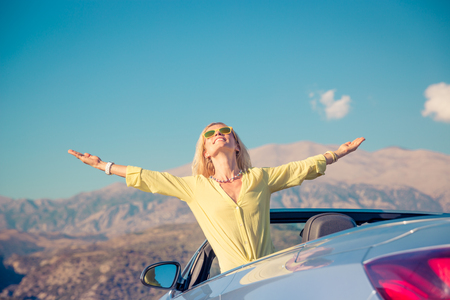 1 person: Happy woman travel by car in the mountains on summer vacation.