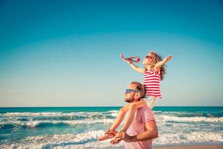 Bonne famille sur la plage. Les gens s'amusent pour les vacances d'été. Père et enfant contre la mer bleue et le fond du ciel. Concept de voyage de vacances Banque d'images - 78590219