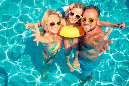 Família feliz se divertindo nas férias de verão. Pai, mãe e criança brincando na piscina. Conceito de estilo de vida saudável ativo