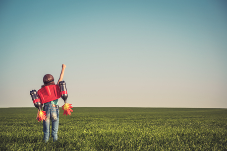 Kid with jet pack outdoor. Child playing in green spring field. Success, imagination and innovation technology concept. Summer travel and adventure Archivio Fotografico