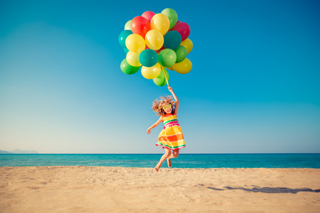 aspirational: Happy child jumping with colorful balloons on sandy beach. Portrait of funny girl against blue sea and sky background. Active kid having fun on summer vacation. Freedom and imagination concept
