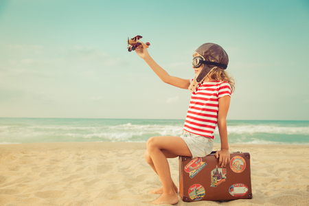 1 person: Happy child playing with toy airplane against sea and sky background. Kid pilot having fun outdoor. Summer vacation and travel concept. Freedom and imagination