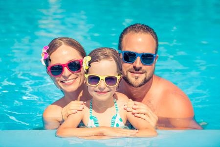 Glückliche Familie, die Spaß auf Sommerferien hat. Vater, Mutter und Kind spielen im Schwimmbad. Aktives gesundes Lifestyle-Konzept