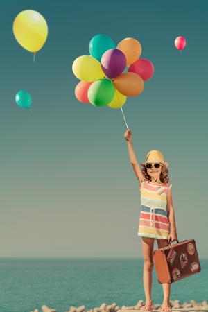 カラフルな風船で遊ぶ幸せな子。青い海と空の背景ヴィンテージ スーツケースと一緒に旅行の女の子の肖像画。子供の夏休みに楽しい時を過します