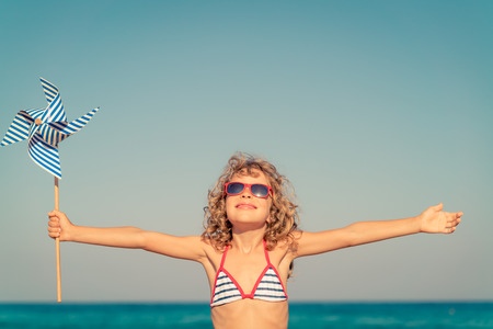 voyage: Happy child with open hands against blue sea and sky background. Kid having fun on summer vacation. Freedom and imagination concept Banque d'images