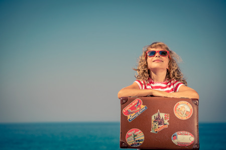 aspirational: Happy child with vintage suitcase. Kid having fun on summer vacation. Travel and adventure concept